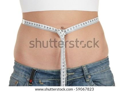 young woman measuring her waist with a measuring tape - stock photo