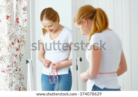 young woman measuring waist with measuring tape in front of a mirror - stock photo