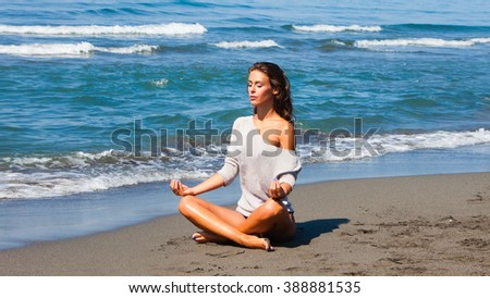 young woman meditate on sandy  beach by the sea full body shot sunny summer day - stock photo