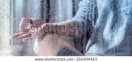 Young woman meditate throw the rain drops - stock photo