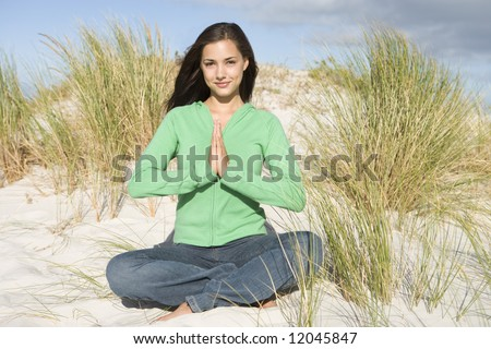 Young woman meditating amongst sand dunes looking to camera - stock photo