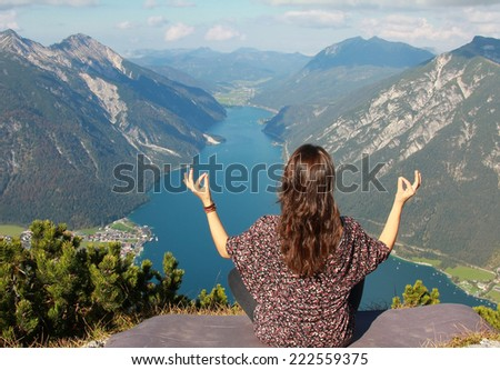 young woman meditating at mountain top with view to lake achensee - stock photo