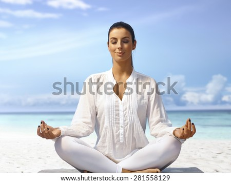 Young woman meditating eyes closed on the beach, smiling. - stock photo
