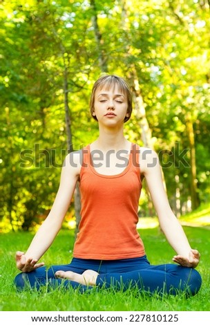 Young woman meditating in half lotus - beautiful park as a background. - stock photo