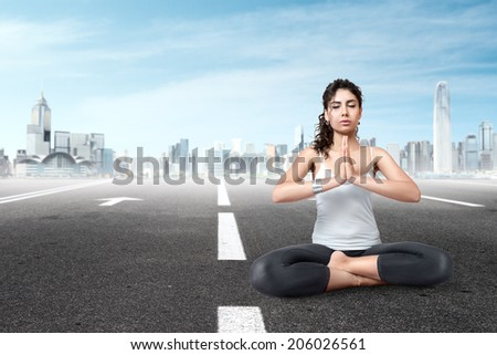 Young woman meditating in lotus position in front of modern city - stock photo