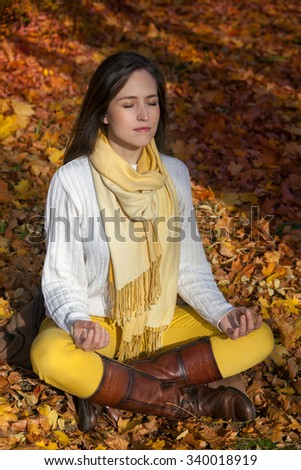 Young woman meditating in lotus position practicing yoga in nature during autumn. Girl doing breathing exercises in park. - stock photo