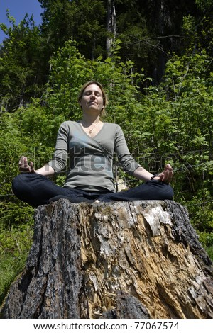 Young woman meditating in the forest. - stock photo