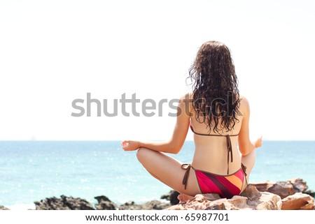 Young woman meditating near ocean - stock photo
