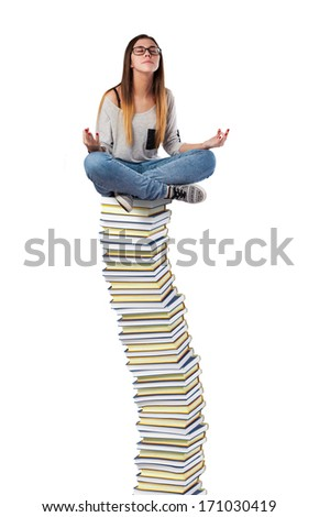 young woman meditating on a books pile - stock photo