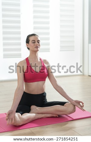 young woman meditating on a carpet in the lotus position, she is in front of a window, the interior is modern and bright - stock photo