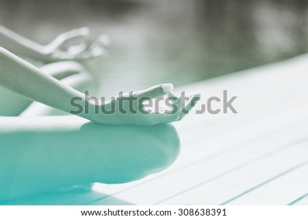 Young woman meditating on a wooden jetty or deck overlooking tranquil green-blue water, close up view of her hands and crossed legs in the lotus position - stock photo