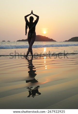 Young woman meditating on Palolem beach. South Goa, India - stock photo