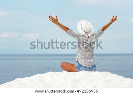 Young woman meditating on the beach in lotus position