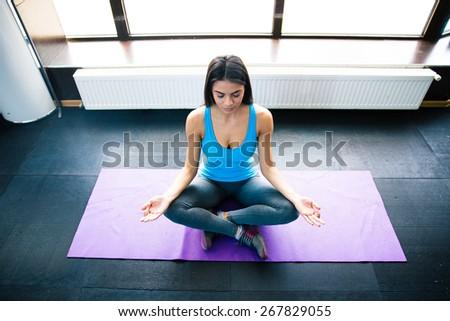 Young woman meditating on yoga mat at gym - stock photo