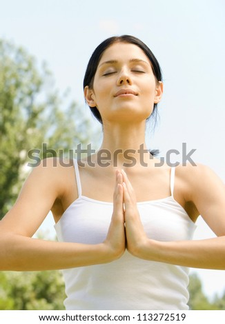 Young woman meditating or praying, outdoor
