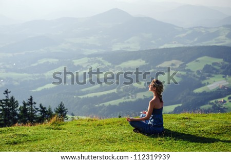 Young woman meditating outdoors - stock photo