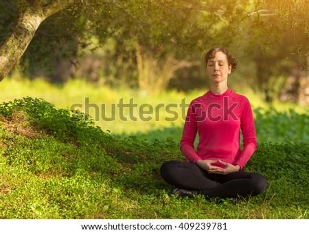 young woman meditating outdoors, selective focus - stock photo