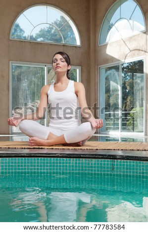 Young woman meditating sitting in lotus position - stock photo