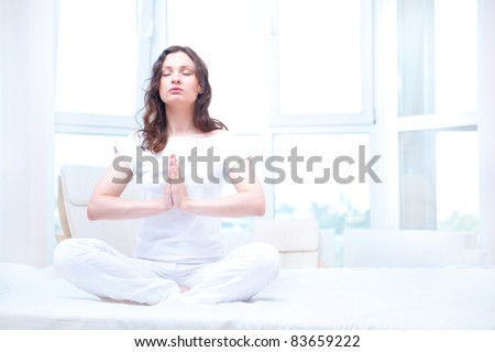 Young woman meditating with closed eyes in bright bedroom sitting on bed - stock photo