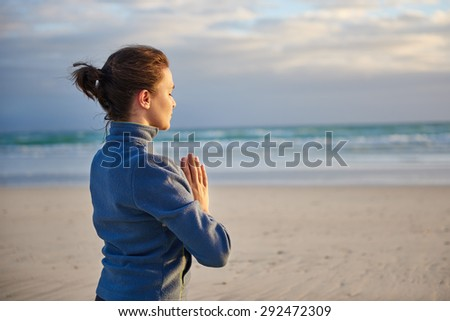 Young woman meditating with her hands together and eyes closed on a beach - stock photo
