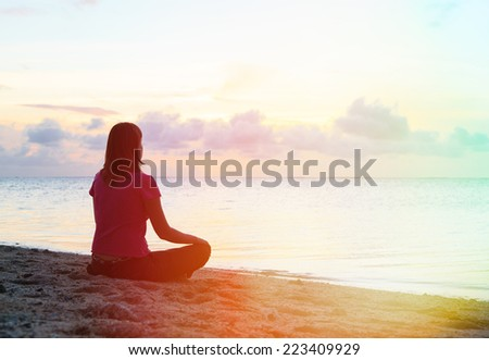 young woman meditation on sunset beach