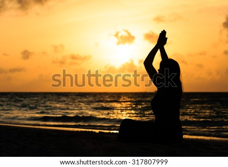 young woman meditation on sunset tropical beach - stock photo
