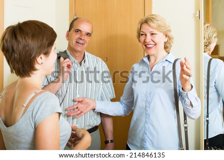 Young woman meeting mature friends at the door  - stock photo
