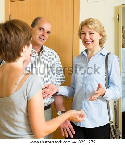 Young woman meeting smiling mature friends couple at the door - stock photo