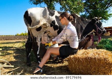 Young woman milking cow on farm