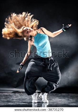 Young woman modern dance. Dark grungy background. - stock photo