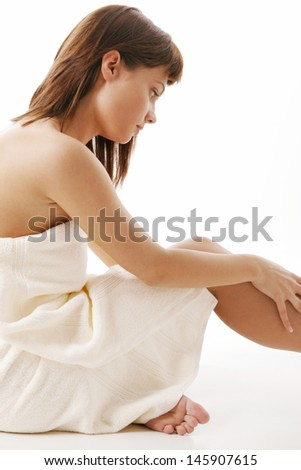 Young woman moisturizing her legs skin
