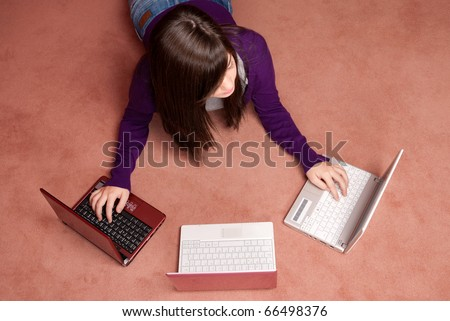 Young woman multitasking with three laptop lying on floor - stock photo