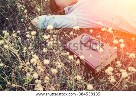young woman napping on the dandelion field after reading book put out glasses on the book - stock photo