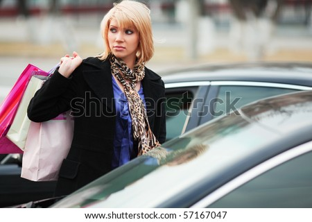 Young woman near a her car after shopping. - stock photo