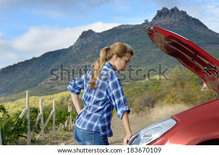 Young woman near broken car needs assistance looking under opened hood - stock photo