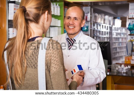 Young woman near counter in pharmacy drugstore  - stock photo