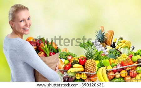 Young woman near shopping cart with food.
