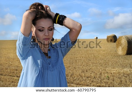 Young woman near the straw bales. England. - stock photo