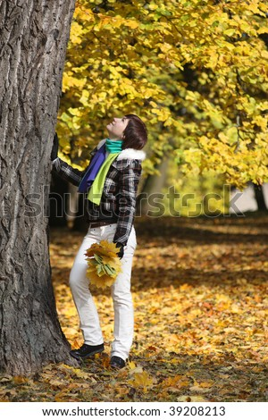 Young woman near the tree in a autumn forest - stock photo