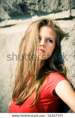 Young woman near the wall portrait. - stock photo