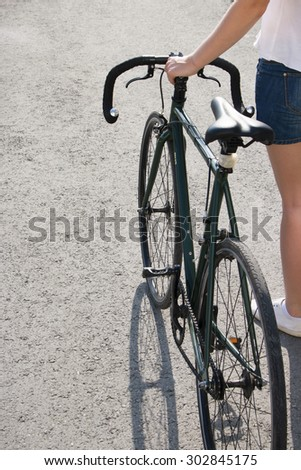 young woman next to a city bicycle selective focus - stock photo