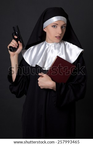 young woman nun with bible and gun over grey - stock photo
