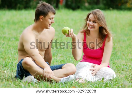 Young woman offer green apple to her beloved - stock photo
