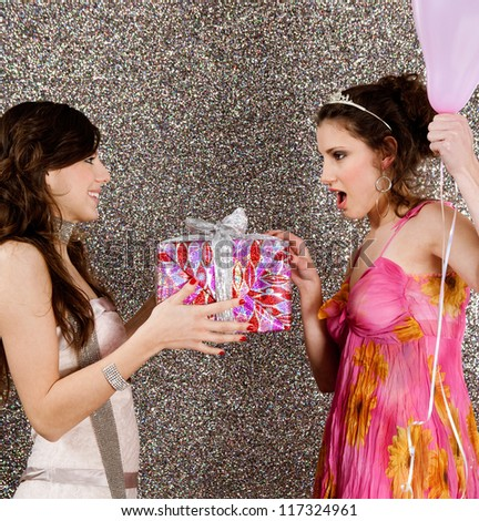Young woman offering a gift to a birthday girl at a party, against a silver glitter background.