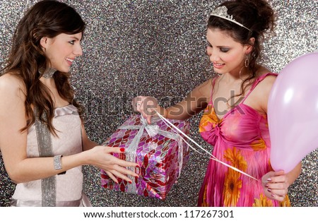 Young woman offering a gift to a birthday girl at a party. Girl opening a birthday present against a silver glitter background. - stock photo