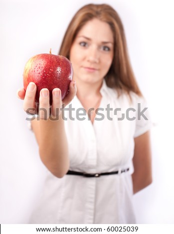 young woman offering an apple ,selective focus