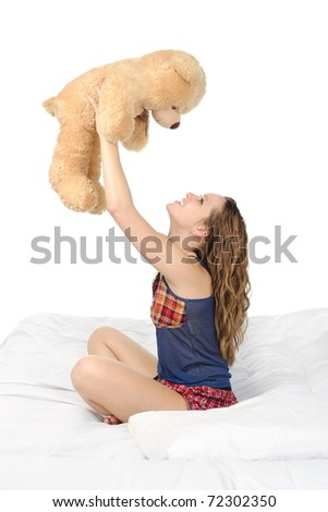 Young woman on a bed in an embrace with teddybear. Isolated on white background - stock photo