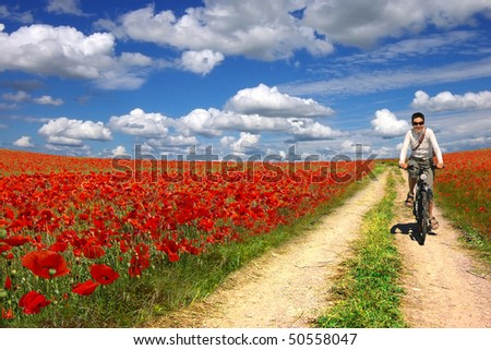 Young woman on a bicycle on a background of the poppies plantation - stock photo