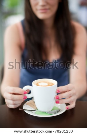 Young woman on a coffee break. Selective focus on the coffee cup. - stock photo