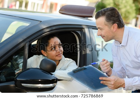 young woman on a driving test with her instructor